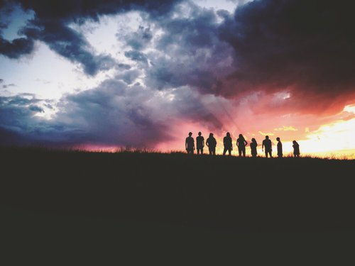 Silhouettes of 9 young people on a hill at sunset