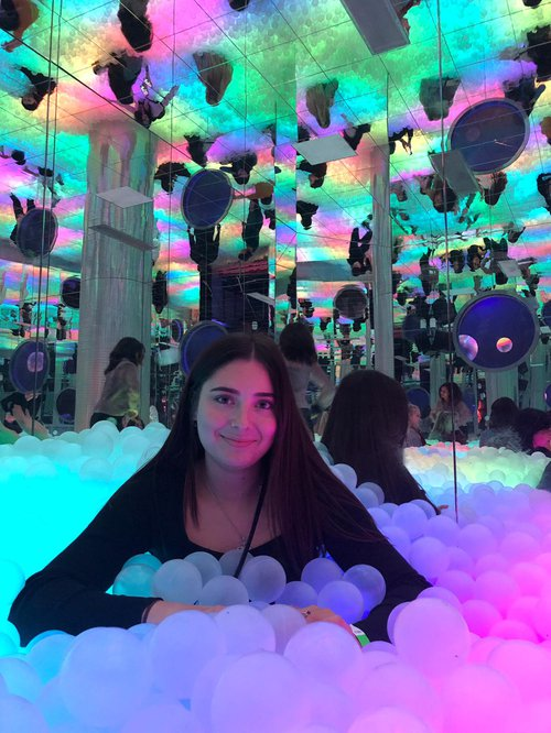 Girl in a ball pit with fluorescent lights