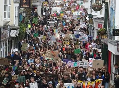 Large group of young people marching in street with signs