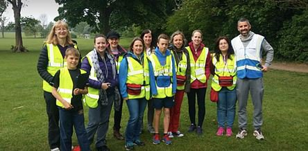 Group of adults and children in green area wearing hi-vis jackets
