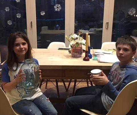 Two dark haired children sitting at kitchen table